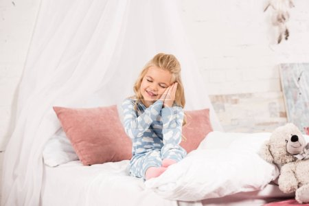 adorable sleepy child sitting on bed with closed eyes