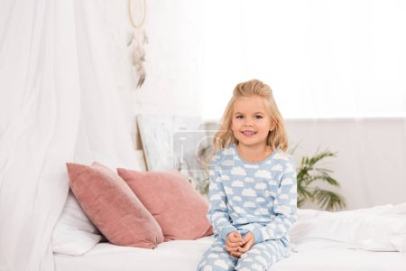 Photo pour Adorable enfant souriant, assis sur le lit matin - image libre de droit