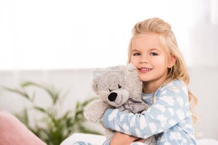 Photo for Adorable child hugging teddy bear in bedroom - Royalty Free Image