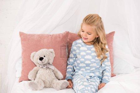 Photo pour Mignon enfant souriant assis sur le lit et regardant ours en peluche - image libre de droit
