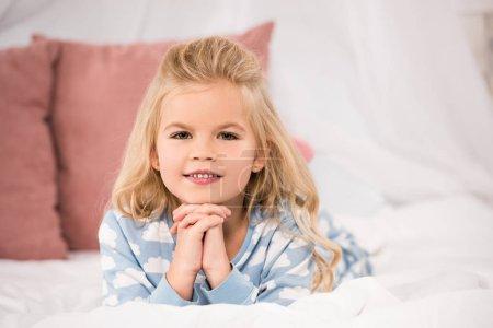 Photo pour Mise au point sélective de mignon enfant en pyjama couché dans son lit - image libre de droit