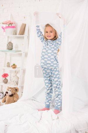 Photo pour Gamin souriant en pyjama debout sur le lit et toucher la verrière - image libre de droit