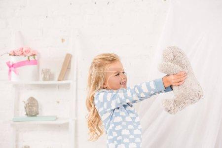 Foto de Sonriente a niño lindo jugando con oso de peluche en el dormitorio - Imagen libre de derechos