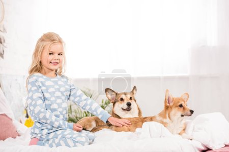 Photo for Adorable kid in pajamas petting corgi dogs in bed - Royalty Free Image