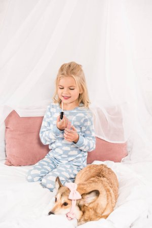 cute child looking at lip gloss while corgi dog with pink accessories lying in bed