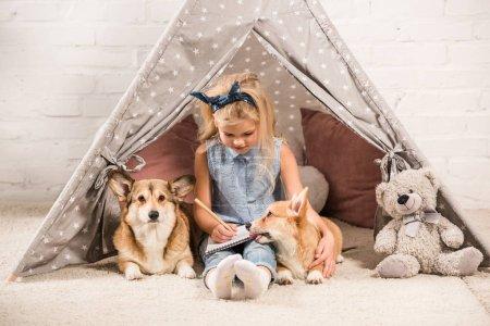 Photo pour Mignon enfant assis avec des chiens corgi en wigwam et écrit dans un carnet à la maison - image libre de droit