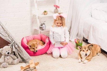 Photo pour Enfant mignon en serre-tête oreilles de lapin assis avec welsh corgi chiens à la maison et l'écriture dans carnet - image libre de droit