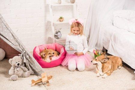 Photo pour Enfant en serre-tête oreilles de lapin assis avec welsh corgi chiens à la maison et l'écriture dans carnet - image libre de droit
