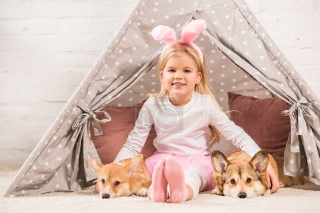 smiling child in bunny ears headband sitting with corgi dogs and teddy bear in wigwam