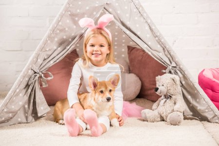 Photo for Cute child in bunny ears headband sitting with corgi dog and teddy bear in wigwam - Royalty Free Image
