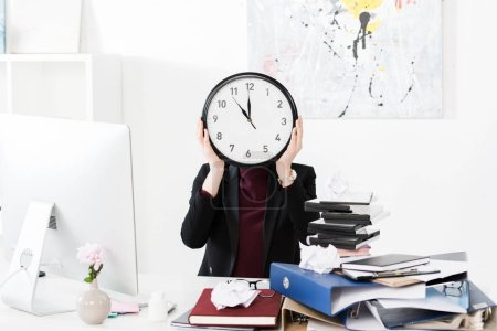 Photo for Businesswoman covering face with clock in office - Royalty Free Image