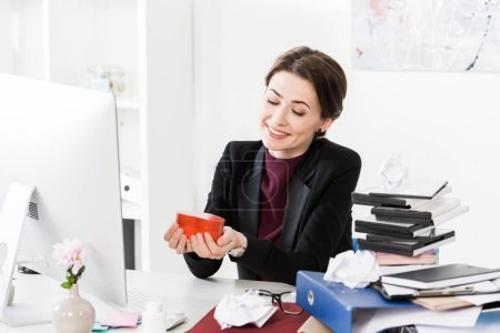 Photo pour Heureuse femme d'affaires attrayant tenant coeur en forme rouge boîte présent au bureau - image libre de droit