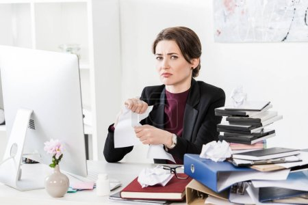sad attractive businesswoman tearing documents in office