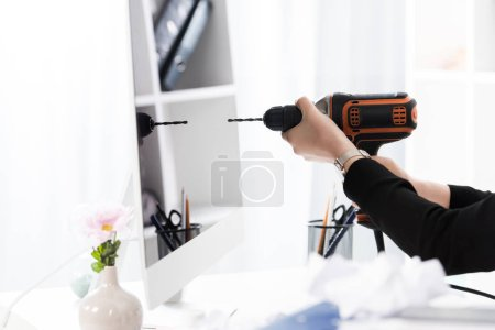 cropped image of businesswoman going to drill computer with electric drill in office