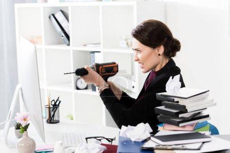 Photo pour Vue latérale d'une femme d'affaires attrayant en colère tenant électrique percer au bureau - image libre de droit