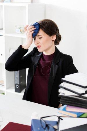Photo pour Femme d'affaires malsaine toucher la tête avec la banquise en bureau - image libre de droit