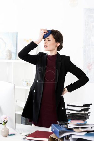 Photo for Exhausted businesswoman having headache and touching head with ice pack in office - Royalty Free Image