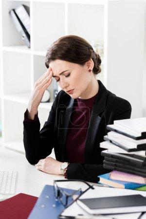 Photo pour Séduisante femme d'affaires ayant des maux de tête et de toucher la tête dans le bureau - image libre de droit