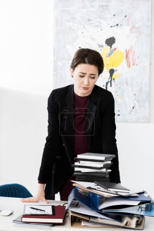 Photo for Sad tired attractive businesswoman looking at pile of documents in office - Royalty Free Image