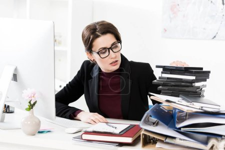 attractive businesswoman in glasses looking at stack of documents in office