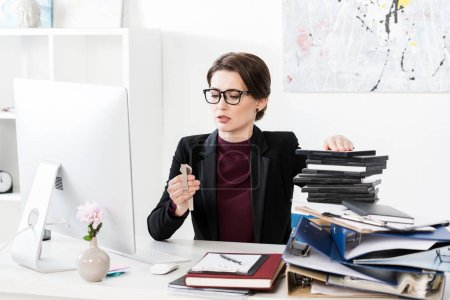 Photo pour Femme d'affaires attrayant lors de montre-bracelet à table dans le bureau de vérification - image libre de droit