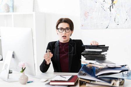Photo pour Femme d'affaires attrayant choqué tenant montre-bracelet au bureau - image libre de droit