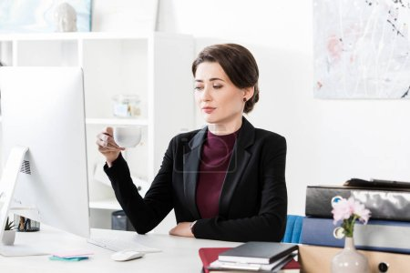 Photo for Attractive businesswoman holding cup of coffee at table in office - Royalty Free Image