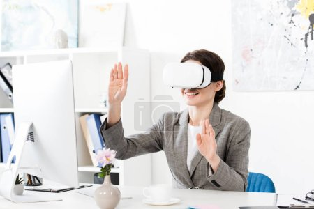Photo for Smiling businesswoman using virtual reality headset in office - Royalty Free Image