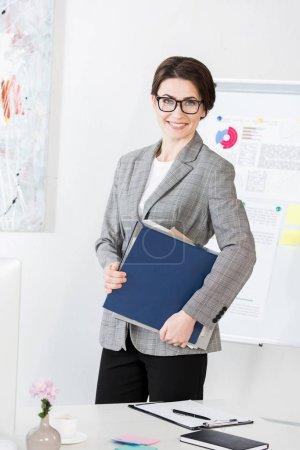 Photo pour Sourire dossier tenue séduisante femme d'affaires avec des documents au bureau - image libre de droit