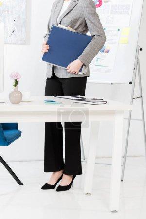 Foto de Sección baja de empresaria sosteniendo la carpeta con los documentos en la oficina - Imagen libre de derechos