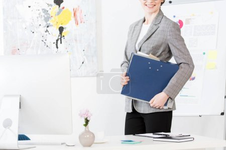 Photo for Cropped image of smiling businesswoman holding folder with documents in office - Royalty Free Image