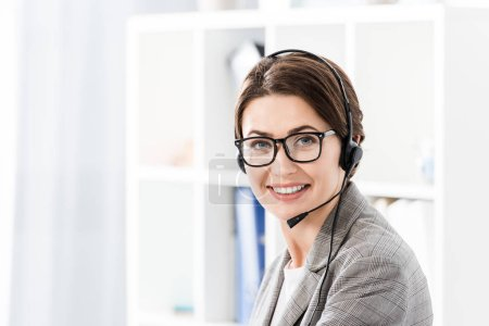 smiling attractive call center operator in glasses and headset looking at camera in office
