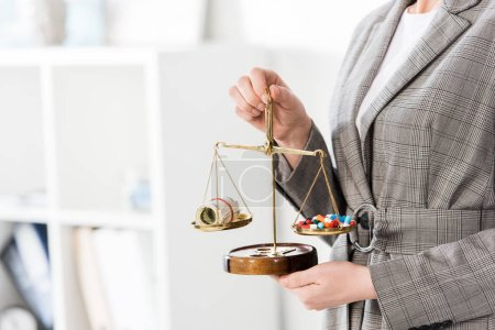 cropped image of lawyer holding justice scales with money and drugs on table in office