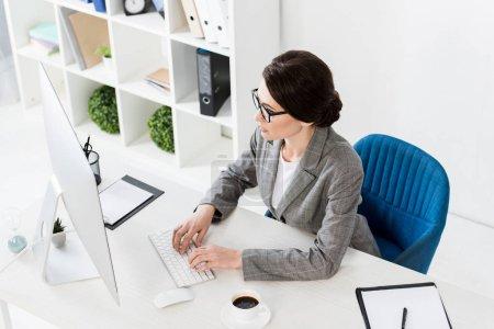 Photo pour Vue d'angle élevé de femme d'affaires attrayant à l'aide d'ordinateur à table dans le bureau - image libre de droit