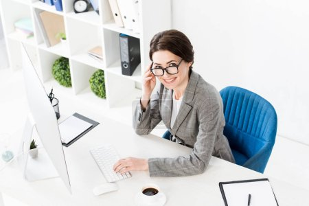 Photo for High angle view of smiling attractive businesswoman using computer at table in office and looking at camera - Royalty Free Image