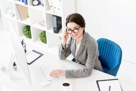 Photo pour Vue grand angle de sourire femme d'affaires attrayante en utilisant l'ordinateur à la table dans le bureau et en regardant la caméra - image libre de droit