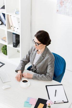 Photo pour Vue d'angle élevé de femme d'affaires attrayant regardant loin de la table au bureau - image libre de droit