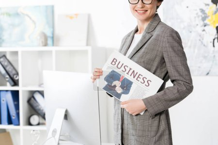 Photo for Cropped image of smiling businesswoman holding newspaper in office - Royalty Free Image
