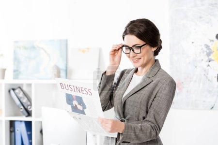 Photo pour Souriant attrayant femme d'affaires lecture journal dans le bureau - image libre de droit