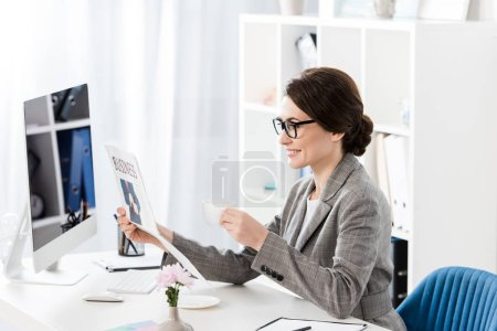 Photo for Side view of attractive businesswoman reading newspaper and holding cup of coffee in office - Royalty Free Image