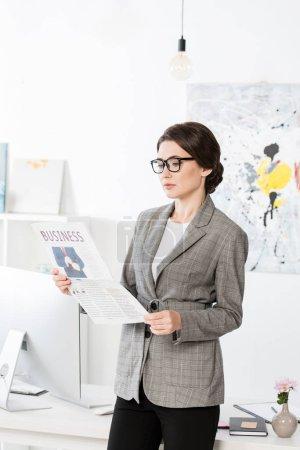 Photo pour Femme d'affaires attrayant lire journal d'affaires au bureau - image libre de droit