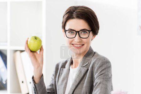 Photo for Portrait of attractive businesswoman holding apple in office and looking at camera - Royalty Free Image