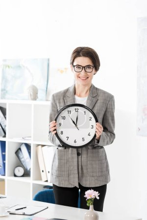 smiling beautiful businesswoman holding wall clock and looking at camera in office