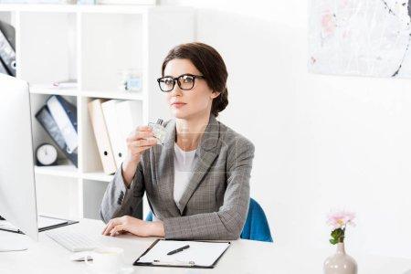 Photo pour Femme d'affaires attrayant reniflant pot de parfum au bureau - image libre de droit