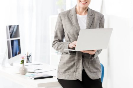 Photo for Cropped image of smiling businesswoman using laptop in office - Royalty Free Image