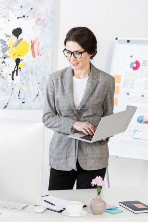 Photo pour Femme d'affaires attrayant tenant ordinateur portable au bureau - image libre de droit