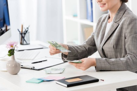 cropped image of businesswoman counting euro banknotes at table in office