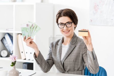 attractive businesswoman showing euro banknotes and credit card in office