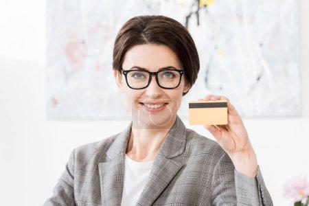Photo pour Attrayant femme d'affaires dans des lunettes montrant carte de crédit et regardant la caméra dans le bureau - image libre de droit