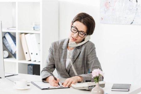 Photo pour Souriante séduisante femme d'affaires dans des verres de parler par téléphone fixe au bureau - image libre de droit